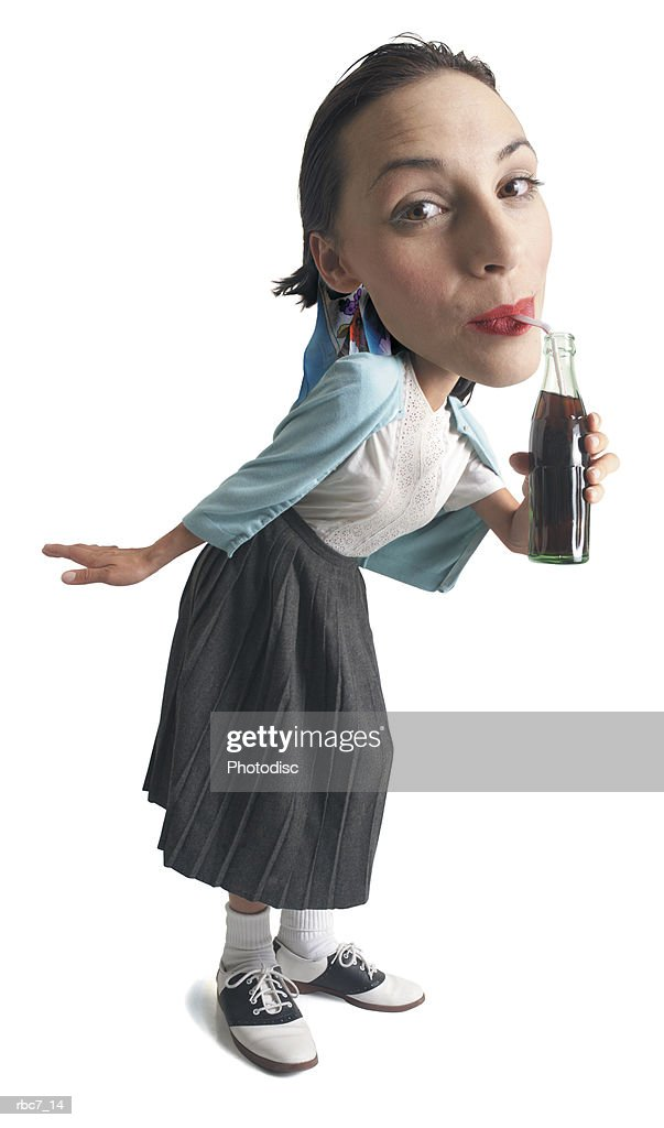 photo caricature of a young girl dressed in 50s retro clothes leans in drinks from a soda bottle : Stock Photo