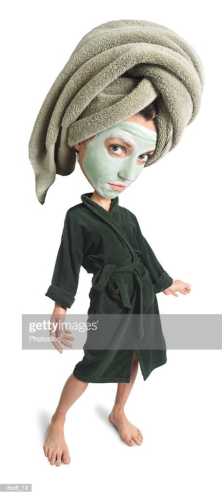 photo caricature of an adult caucasian woman in a green face mask and bathrobe with a towel on her head : Stockfoto