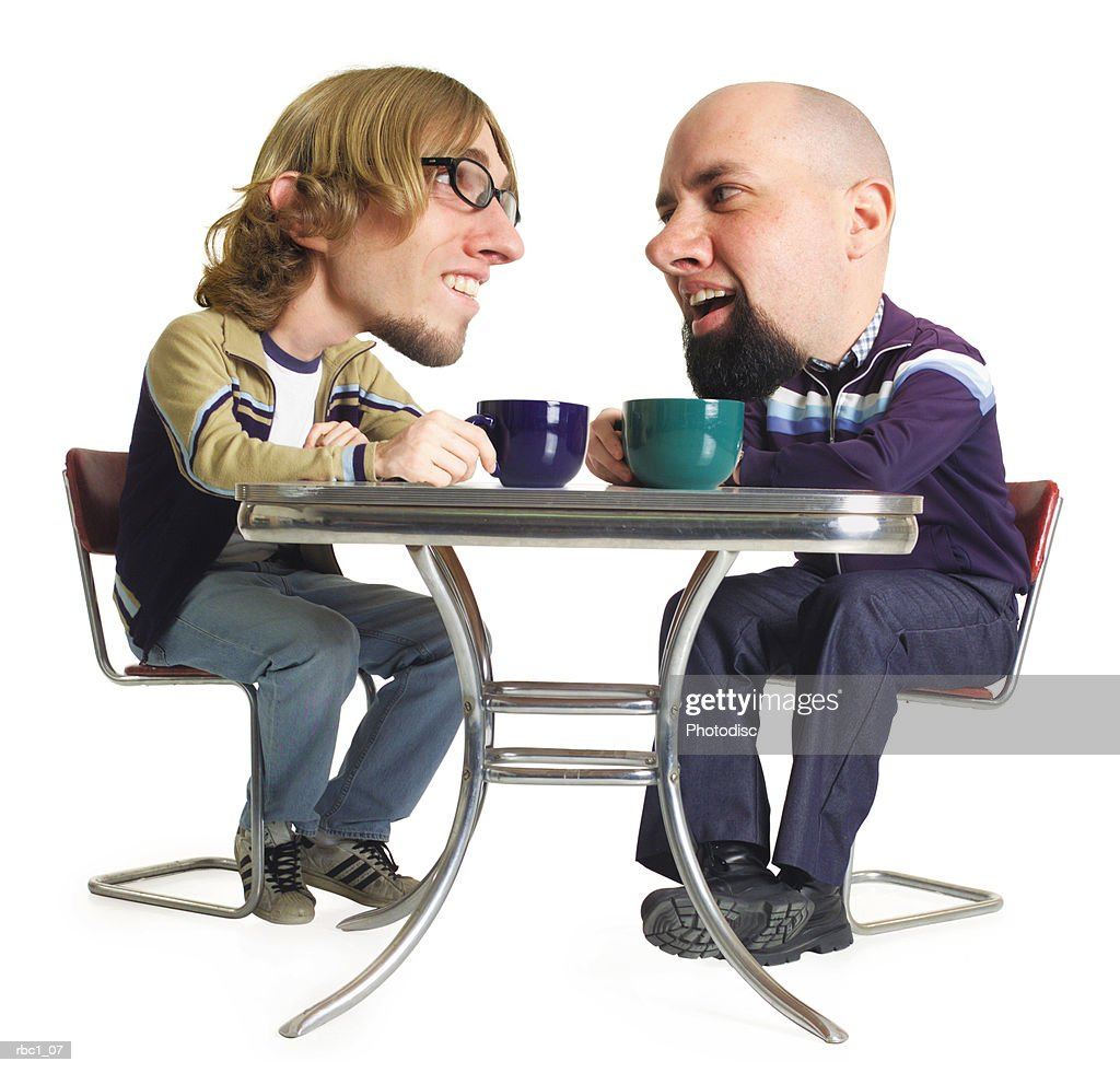 photo caricature of two young caucasian male friends as they sit at a table with their coffee mugs and converse : Stockfoto