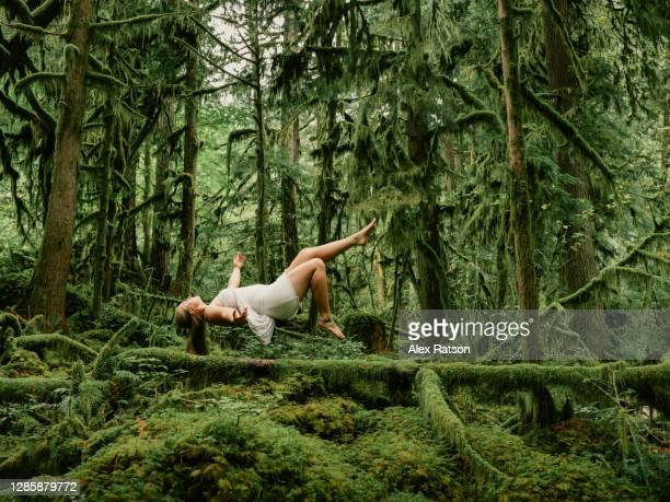 photo composite of a young female in a white dress floats mid air on her back in a lush coastal rainforest - releasing stock pictures, royalty-free photos & images
