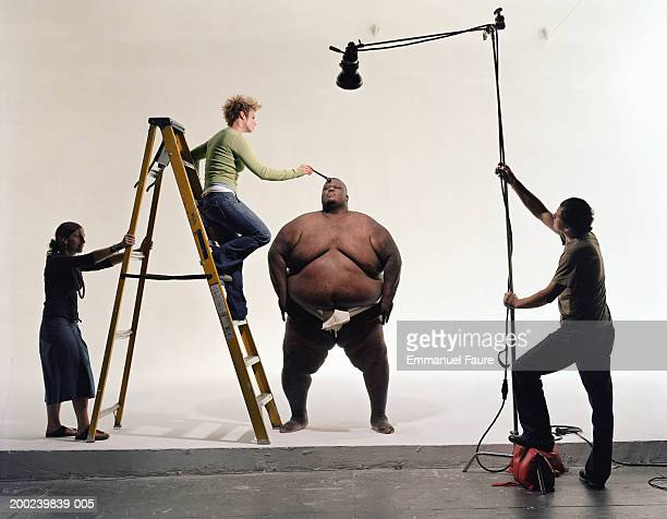Photo crew preparing sumo wrestler for filming