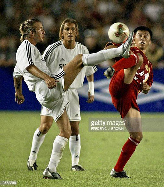 Photo dated 02 august 2003 shows Real Madrid's David Beckham vying for the ball with Liu Yue of the Chinese Dragons during the England captain's...