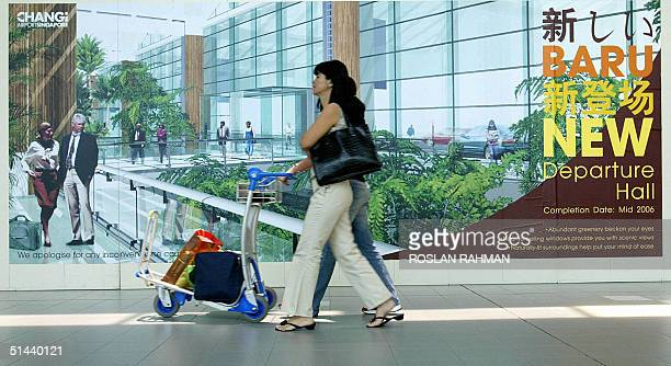 Photo dated 24 September 2004 shows passengers walking past a poster featuring the new look of the departure hall at Changi International Airport...