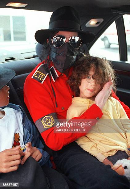 Photo dated May 13 1993 shows US pop star Michael Jackson with his face covered with a scarf and wearing sunglasses holding an unidentified child and...