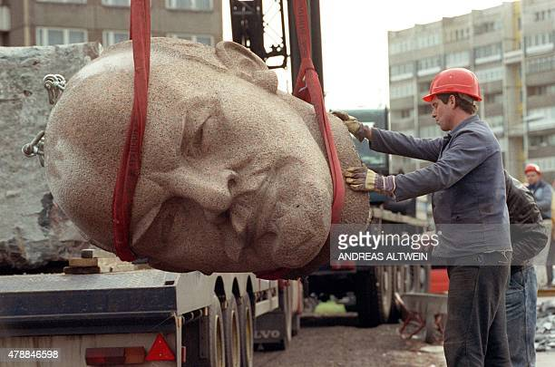 A photo dated November 13 shows a worker removing the head of a statue representing late Soviet leader Vladimir Ilyich Lenin during its demolition on...