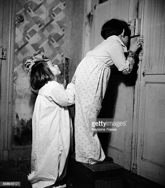Photo de propagande ici des enfants regardant par le trou de la serrure à Vichy France circa 1940