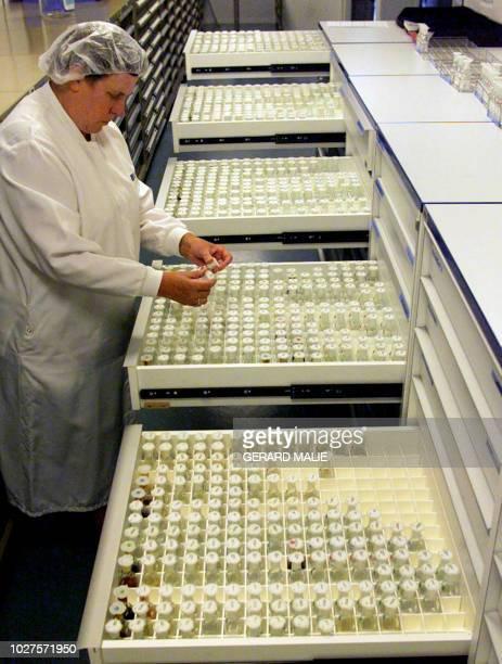 . Photo d'une laborantine contrôlant des flacons dans la salle des diluthèques, le 02 août 2001, sur le site des laboratoires Boiron à...