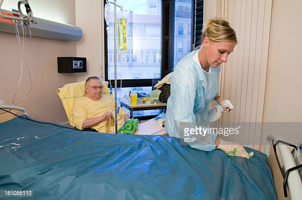 Photo Essay At Saint Louis Hospital, Paris, France. Department Of Endocrinology. Washing Of The Anti Bed Sore Mattress Before Changing The Bedding.