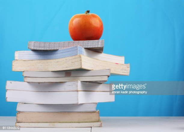 photo for books on table with apple in blue wall background - school supplies stock pictures, royalty-free photos & images