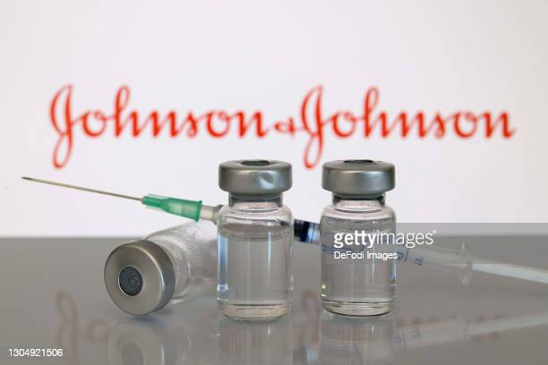 Photo Illustration A syringe lies on a bottle of fluid in front of Johnson und Johnson's logo due to Johnson und Johnson's new vaccine against...