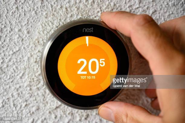Photo illustration of a hand adjusting a Google Nest smart thermostat to adjust the temperature in the living room on October 12,2021 in Kampen,...