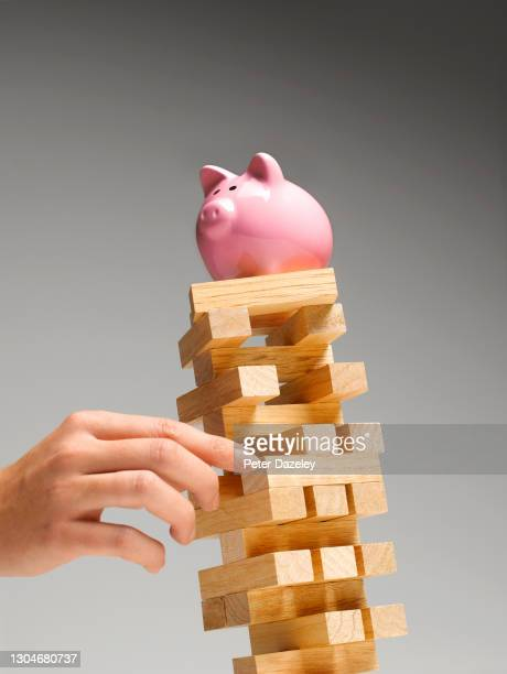 Photo illustration of a leaning tower with piggy bank balanced on top on February 1,2021 in London, England.