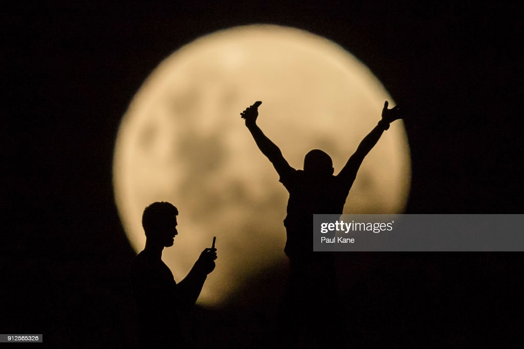 Photo Illustration showing people taking photos of the Super moon on January 31, 2018 in Lancelin, Australia. Last seen from Australia in December 1983, a Super Blue Blood Moon is the result of three lunar phenomena happening all at once. Not only is it the second full moon in January, but the moon will also be close to its nearest point to Earth on its orbit, and be totally eclipsed by the Earth's shadow.