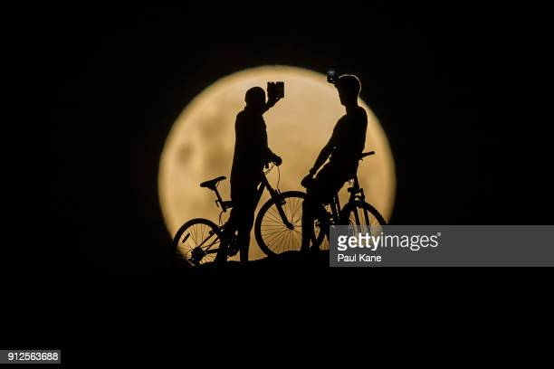 Photo Illustration showing people with bicycles taking photos of the Super moon on January 31 2018 in Lancelin Australia Last seen from Australia in...