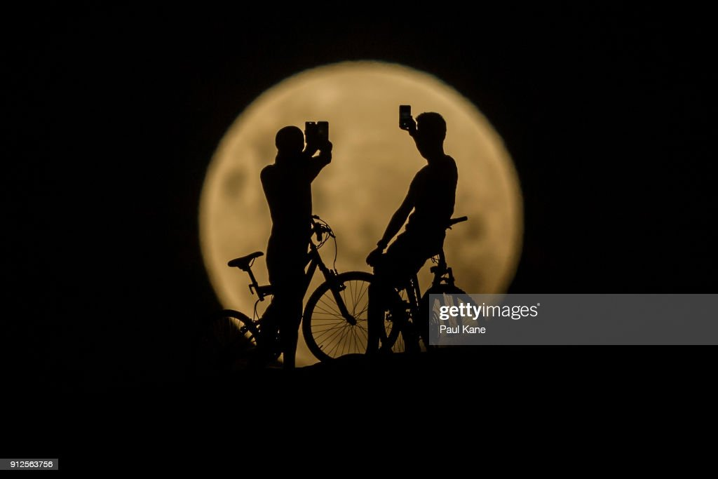 Photo Illustration showing people with bicycles taking photos of the Super moon on January 31, 2018 in Lancelin, Australia. Last seen from Australia in December 1983, a Super Blue Blood Moon is the result of three lunar phenomena happening all at once. Not only is it the second full moon in January, but the moon will also be close to its nearest point to Earth on its orbit, and be totally eclipsed by the Earth's shadow.