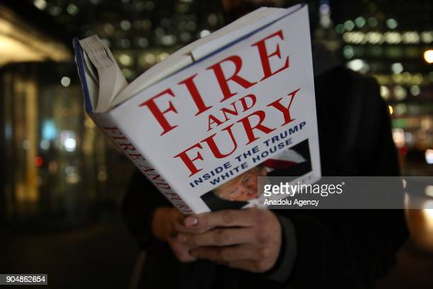 A photo illustration shows a man posing with a book titled 'Fire and Fury' that criticizes US President Donald J Trump in Manhattan in New York...