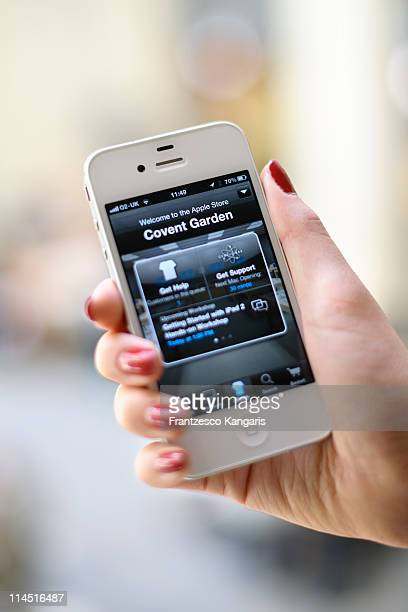 A photo illustration shows a woman displaying the new Apple Store iPhone app at Apple Store Covent Garden on May 23 2011 in London England