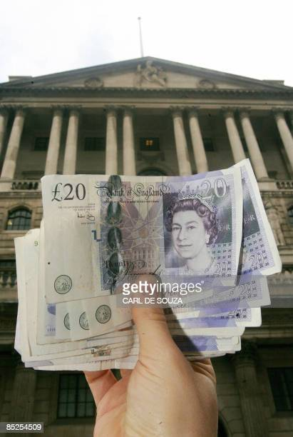 A photo illustration shows British sterling notes held against a backdrop of the Bank of England in London on March 5 2009 The Bank of England said...