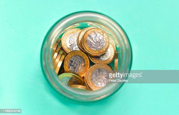 A photo illustration showsBritish currency coins savings in jar shot from above on August 192019 in LondonEngland