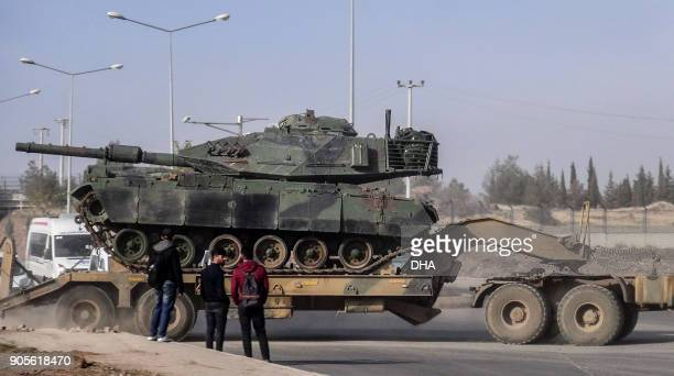 A photo made available by the Dogan New Agency shows Turkish army military trucks transporting armoured vehicles to reinforce the border units in...
