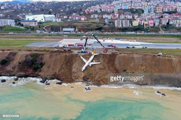 A photo made available by the Dogan New Agency shows Turkish passenger plane struck in mud on an embankment five days after skidding off the airstrip...