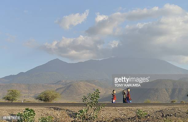 Photo made October 25 2014 shows Maasai women carrying water in jerrycans on their heads as they walk along a road at the foothills of Mt Meru near...
