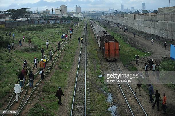 Photo made on May 14 2014 shows people walking along the tracks as a train transporting passengers from the business district of Nairobi approaches...