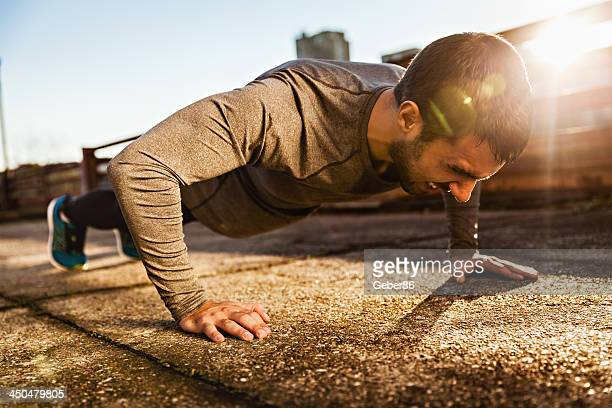 Photo of a athletic man doing push ups outdoors
