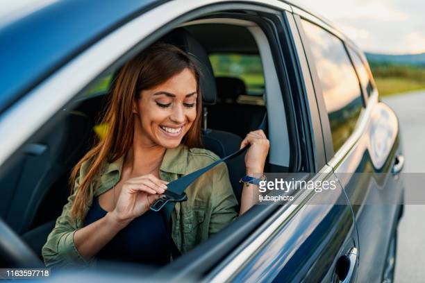 photo of a business woman sitting in a car putting on her seat belt - fastening stock pictures, royalty-free photos & images
