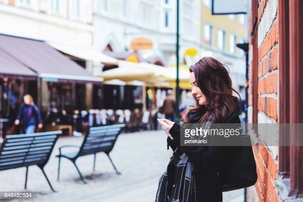 Photo of a business woman using smart phone, city business