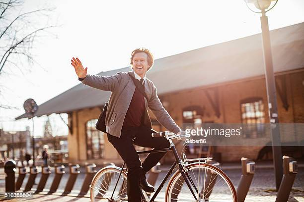 photo of a businessman cycling home from his job - waving gesture stock photos and pictures