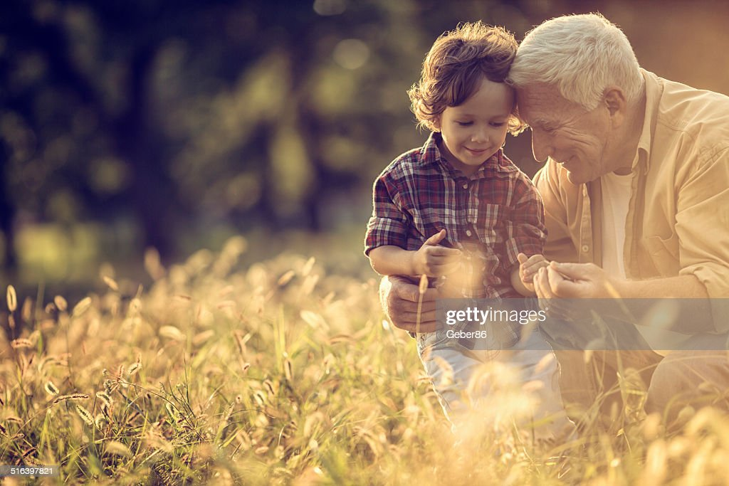 Photo of a cheerful grandfather and his grandson playing outdoors : Stock Photo
