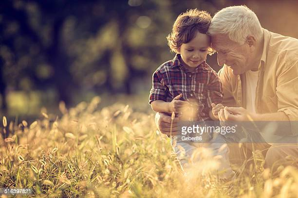 Photo of a cheerful grandfather and his grandson playing outdoors