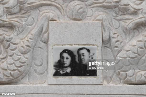 A photo of a couple is seen on a gravestone during the Qing Ming festival also known as Tomb Sweeping Day at a cemetery in Beijing on April 5 2018...