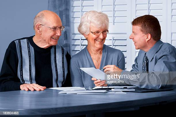 A photo of a financial advisor talking to an elderly couple