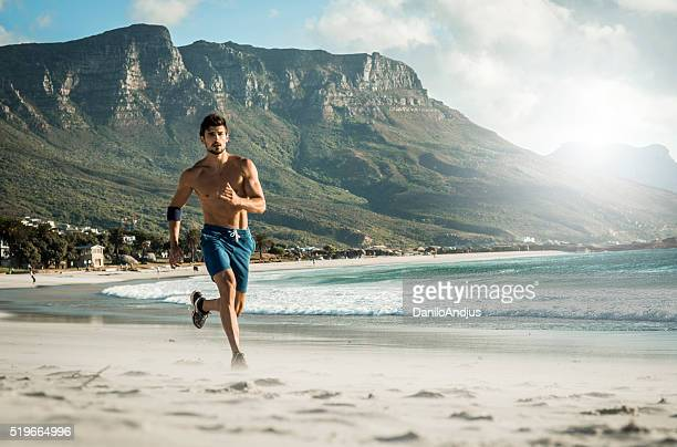 photo of a fit man running on the beach