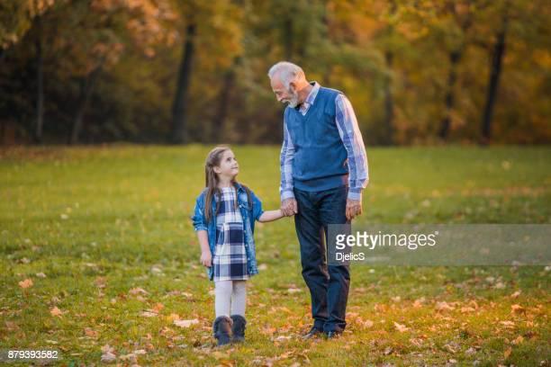 Foto de un abuelo y su nieta dando un paseo en el parque.