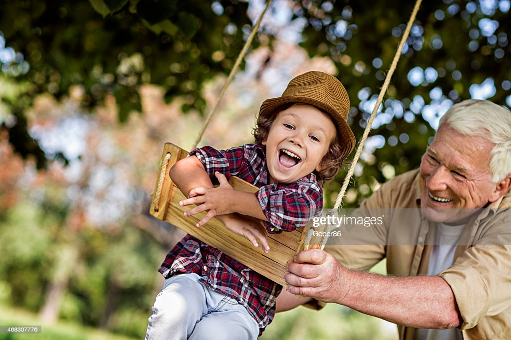 Photo of a grandfather and his grandson on swing : Stock Photo