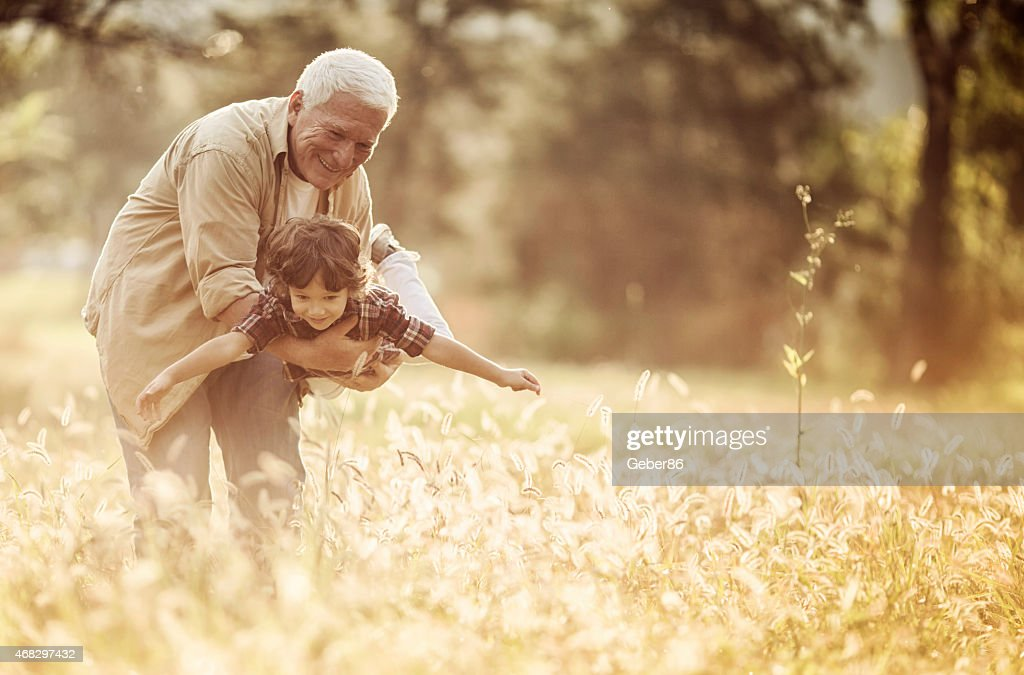 Photo of a grandfather playing with grandson outdoors : Stock Photo