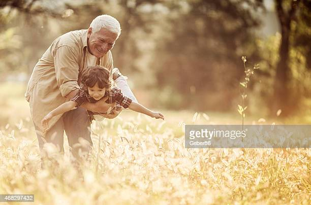 Photo of a grandfather playing with grandson outdoors