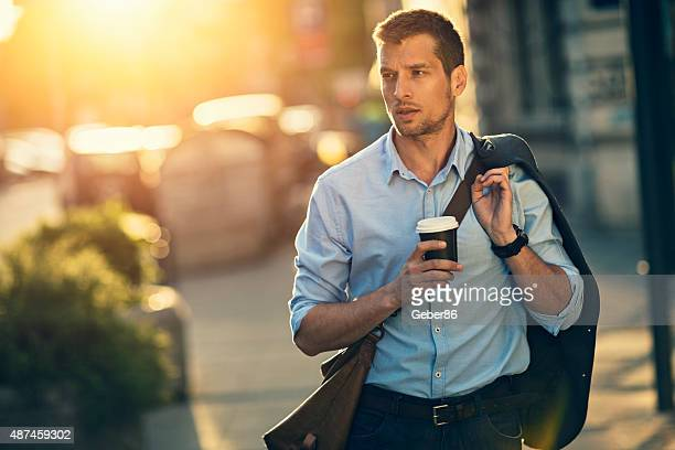 Photo of a handsome man having takeaway coffee in city