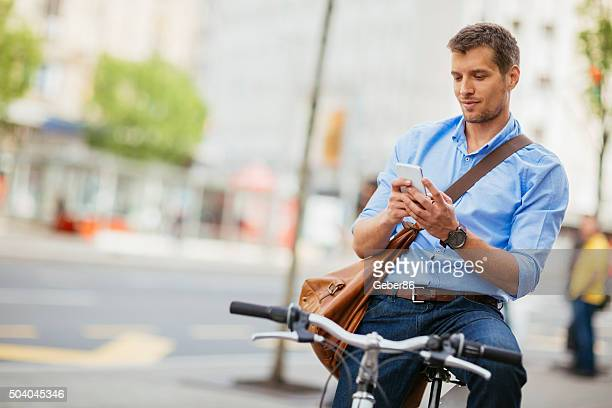 Photo of a handsome man holding smartphone in city