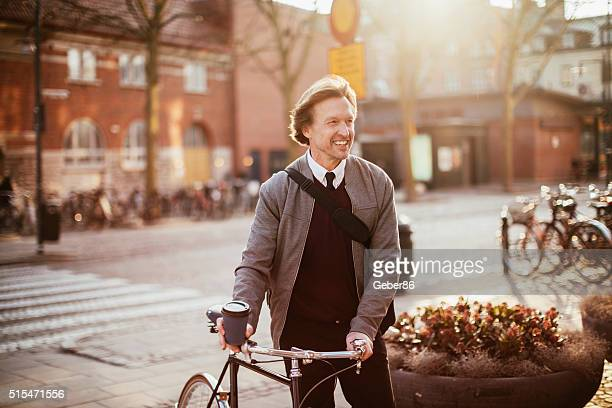 Photo of a handsome man leading his bike