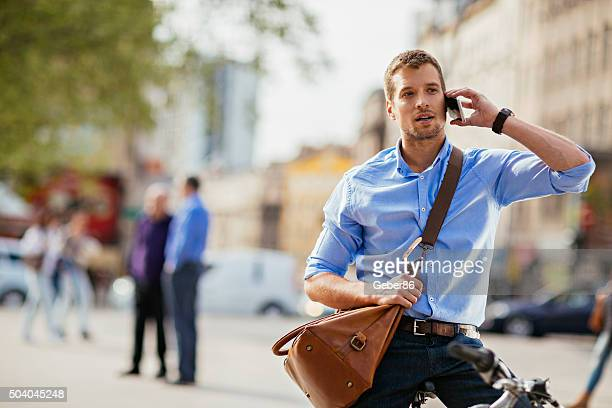 Photo of a handsome man speaking on phone in city