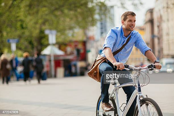 photo of a handsome smiling man riding bike in city - fietsen stockfoto's en -beelden