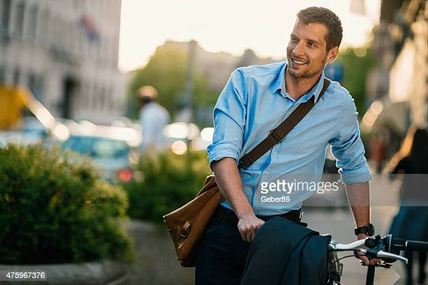 Photo of a handsome smiling man riding bike in city