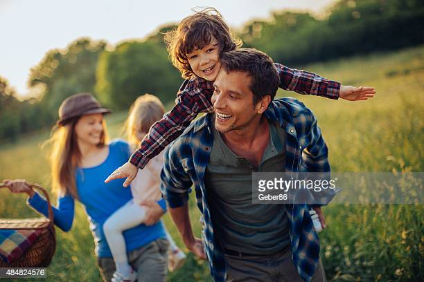 photo of a happy family going for picnic - piggyback stock pictures, royalty-free photos & images