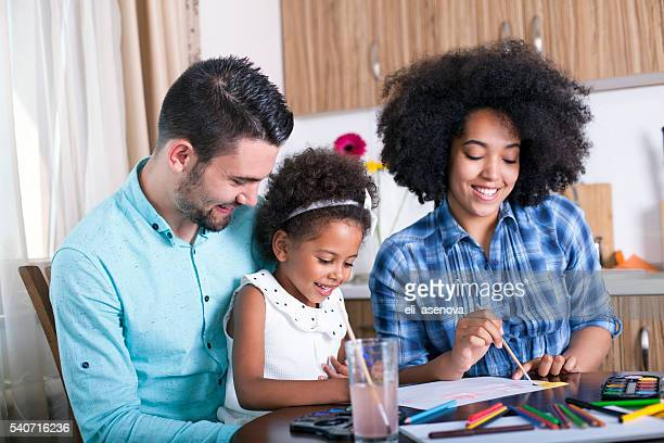 Photo of a happy family paiting with water colorsn