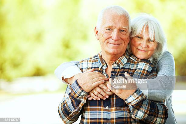 Photo of a happy hugging senior couple in park