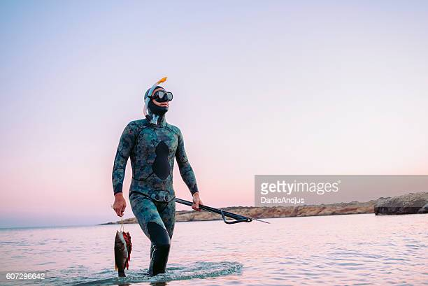 photo of a man coming back from spear fishing